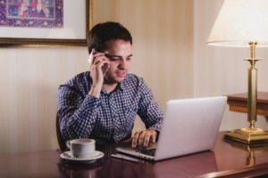 Young sales associate leaving a voicemail for a prospective client & preparing a follow up email