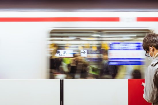 Man glancing at his phone while a subway train speeds by him