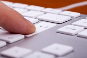 A person's finger pressing the return key on an Apple aluminum keyboard