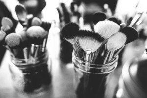 Black & white image of cosmetic brushes arranged inside glass jars