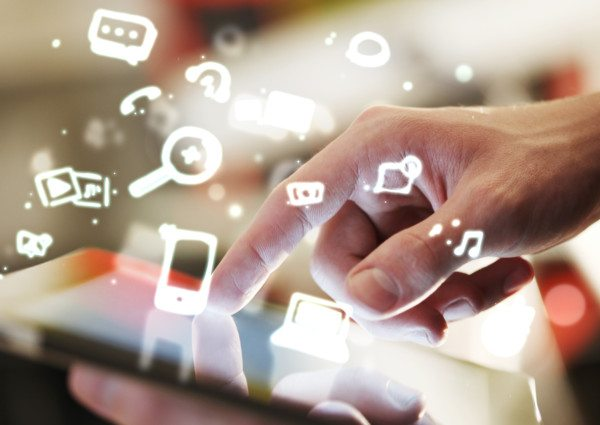 SEO style photo of a user touching his tablet along with illustrated tech images hovering around